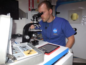 Craig Kutz examines a meteorite sample during one of his 14-hour work days on the mission.