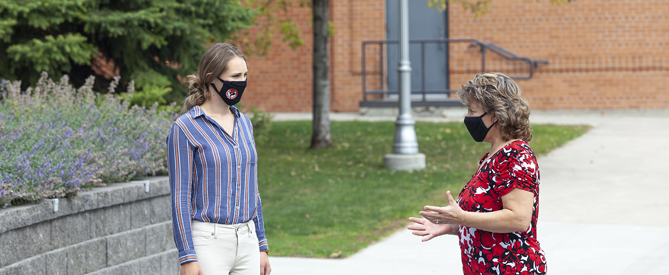 Female mentee and mentor wearing masks talk outside